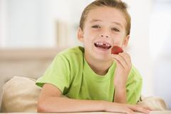 Young boy eating strawberries in living room smiling Stock Photos