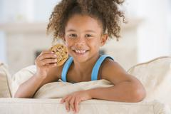 Young girl eating cookie in living room smiling Stock Photos