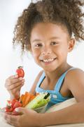 Young girl eating bowl of vegetables in living room smiling Stock Photos
