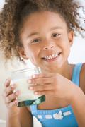 Young girl indoors drinking milk smiling Stock Photos