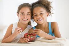 Two young girls eating strawberries in living room smiling Stock Photos