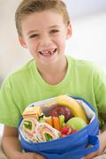 Young boy holding packed lunch in living room smiling Stock Photos