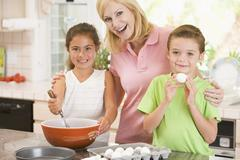 Woman and two children in kitchen baking and smiling - stock photo