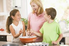 Woman and two children in kitchen baking and smiling Stock Photos