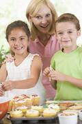 Woman with two children in kitchen decorating cookies smiling Stock Photos