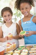 Two children in kitchen decorating cookies smiling Stock Photos