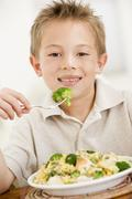 Young boy indoors eating pasta with brocolli smiling Stock Photos