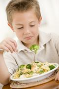 Young boy indoors eating pasta with brocolli - stock photo