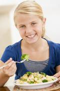 Young girl indoors eating pasta with brocolli smiling Stock Photos