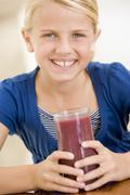 Young girl indoors drinking juice smiling - stock photo