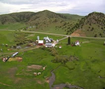 Unsteady aerial shot of mountain farm and outbuildings Stock Footage