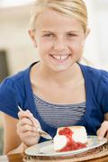 Young girl indoors eating cheesecake smiling Stock Photos