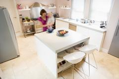 Woman in kitchen whisking on counter holding baby - stock photo