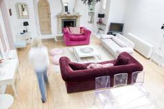 Woman walking through living room - stock photo