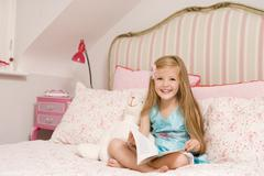 Young girl sitting on bed with book smiling Stock Photos