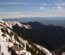 Aerial shot of melting snowy mountains, distant blue sky - stock footage