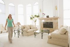 Woman walking through living room Stock Photos