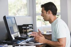 Man in home office using computer looking frustrated Kuvituskuvat