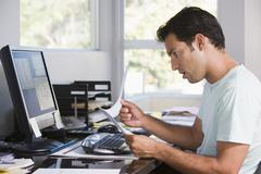 Man in home office using computer holding paperwork and looking shocked - stock photo