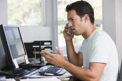 Man in home office on telephone using computer and frowning - stock photo