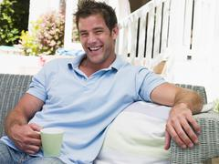 Man sitting on patio with coffee laughing - stock photo