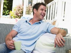 Man sitting on patio with coffee laughing Stock Photos