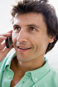 Man using cellular phone and smiling - stock photo