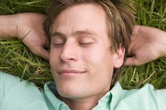 Man lying on grass sleeping - stock photo
