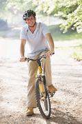 Man outdoors on bike smiling - stock photo