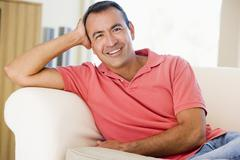 Man sitting in living room smiling Stock Photos