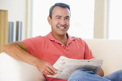 Man reading newspaper in living room smiling - stock photo