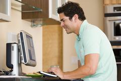 Man in kitchen using computer and smiling Stock Photos