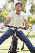 Man outdoors on bike with legs out - stock photo
