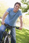 Man outdoors on bike smiling - stock photo