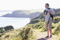 Man standing on cliffside path - stock photo