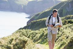 Man walking on cliffside path looking at map - stock photo