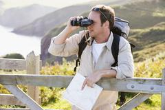 Man relaxing on cliffside path holding map and binoculars - stock photo
