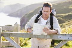 Man relaxing on cliffside path holding map - stock photo
