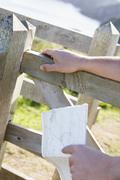 Man's hands on fence holding map - stock photo