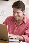 Man in kitchen using laptop smiling Stock Photos