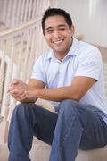 Man sitting on staircase smiling Stock Photos