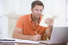 Man in dining room with laptop holding paperwork Stock Photos