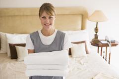 Maid holding towels in hotel room smiling Stock Photos