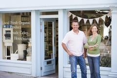 Couple standing in front of organic food store smiling Stock Photos