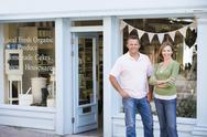 Stock Photo of Couple standing in front of organic food store smiling
