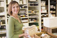 Woman in market looking at bread smiling Stock Photos