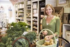 Woman in market looking at potatoes smiling Stock Photos