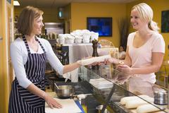 Woman standing at counter in restaurant serving customer and smiling Stock Photos