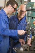 Two machinists working on machine Stock Photos