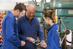 Three machinists in workspace by machine talking Stock Photos
